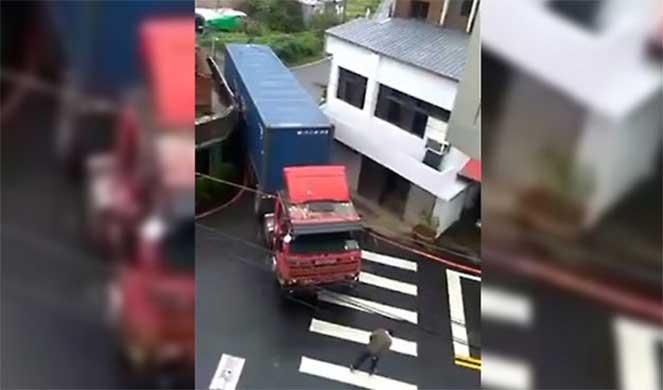 Китайский водитель грузовика виртуозно проходит сквозь узкий просвет между домами